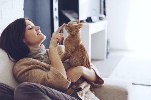Young woman wearing warm sweater is resting with a cat on the ar