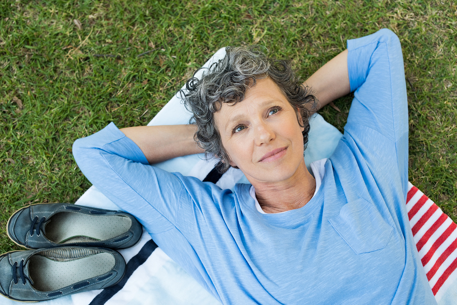 senior woman lying on towel on grass