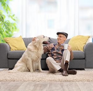 Elderly man sitting on the floor and petting his dog