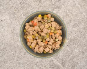 Top view of an old stoneware bowl filled with lamb dog food plus peas and squash on a rough concrete floor.